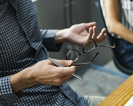 Image of a man's hands gesturing as if explaining something while a woman listens nearby, representing the frustration that can arise and the predicament a California employer may find itself in if it fails to hire an employment lawyer experienced in defending DFEH complaints in California.